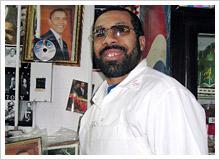 自慢の「オバマコーナー」に立つピザ屋のオーナー、モハマドさん。20日は店で近所の仲間達と盛大に祝う予定
